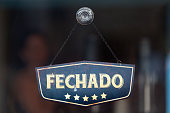 """Old fashioned sign in the window of a shop saying in Portuguese """"Fechado"""", meaning in english """"Closed""""."""