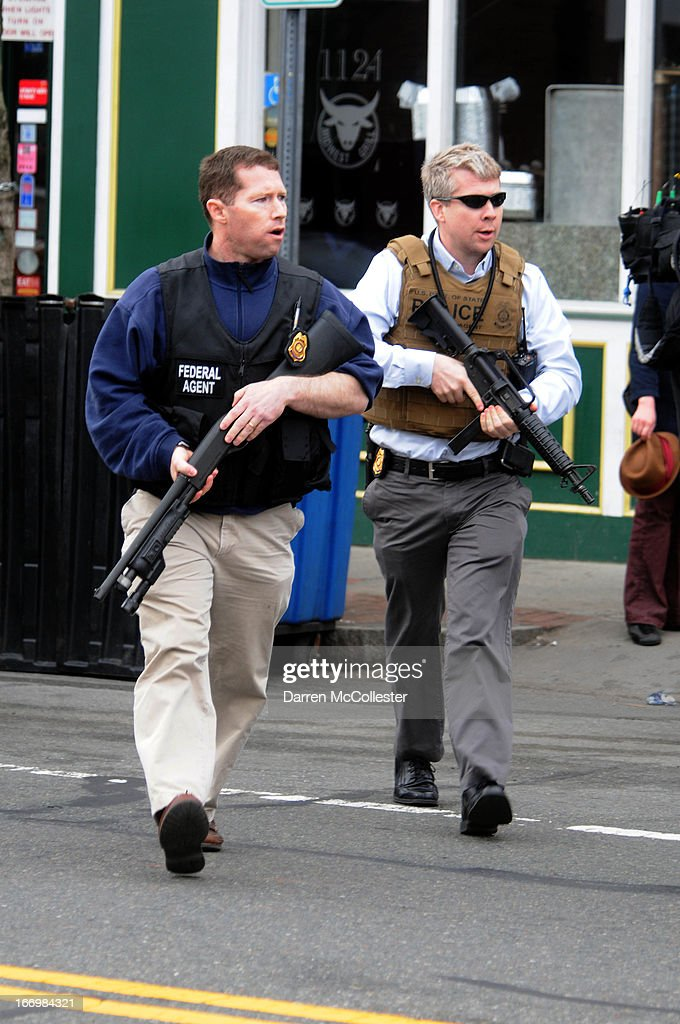 Federal agents descend on the home of a suspect-at-large in the Boston Marathon bombing and nearby Watertown shooting, on Norfolk Street April 19, 2013 in Cambridge, Massachusetts. Earlier, a Massachusetts Institute of Technology campus police officer was shot and killed late Thursday night at the school's campus in Cambridge. A short time later, police reported exchanging gunfire with alleged carjackers in Watertown, a city near Cambridge. According to reports, one suspect has been killed during a car chase and the police are seeking another - believed to be the same person (known as Suspect Two) wanted in connection with the deadly bombing at the Boston Marathon earlier this week. Police have confirmed that the dead assailant is Suspect One from the recently released marathon bombing photographs.