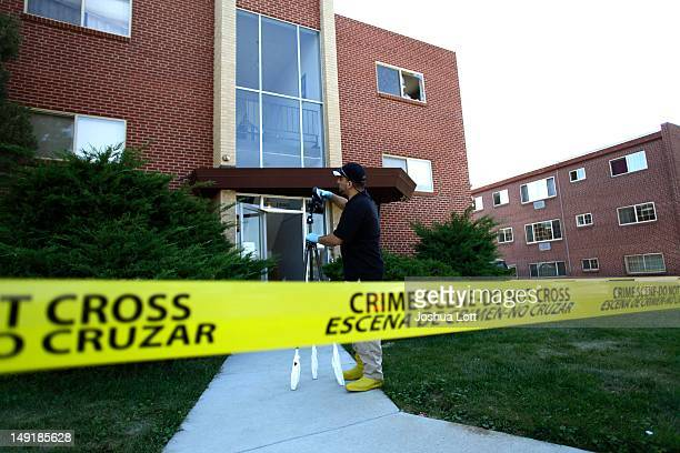 Federal Bureau of Investigation agent takes photos as he investigates outside the apartment building where suspect James Holmes lived July 24 2012 in...