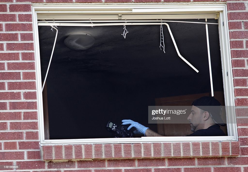 A Federal Bureau of Investigation agent takes photos as he investigates inside the apartment where suspect James Holmes lived July 24, 2012 in Aurora, Colorado. Holmes, 24, is accused of killing 12 people and injuring 58 in a shooting spree on July 20 during a screening of 'The Dark Knight Rises.' According to police Holmes' apartment had more than 30 homemade grenades and 10 gallons of gas inside that was booby-trapped to go off.