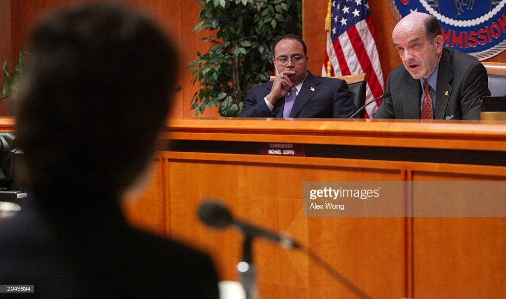 Federal Communications Commission Chairman Michael Powell listens as Commissioner Michael Copps speaks during a board review of rules meeting on...