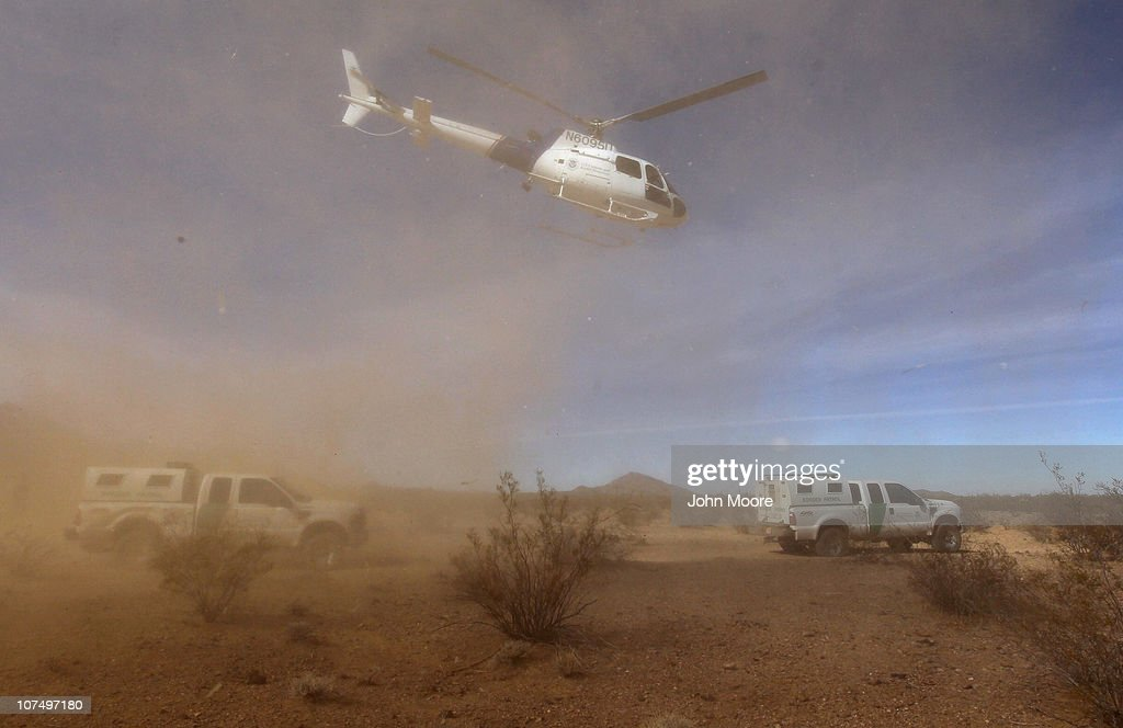 A federal helicopter from the U.S. Office of Air and Marine flies over U.S. Border Patrol vehicles in Sonoran Desert while searching for drug smugglers December 9, 2010 in the Tohono O'odham Reservation, Arizona, near the U.S.-Mexico border. The two federal agencies work closely together in searching for smugglers and illegal immigrants who cross in remote areas all along the U.S.-Mexico border.