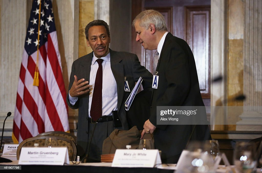 Federal Housing Finance Agency Director Melvin Watt talks to Federal Deposit Insurance Corporation Chairman Martin Gruenberg prior to an open session...
