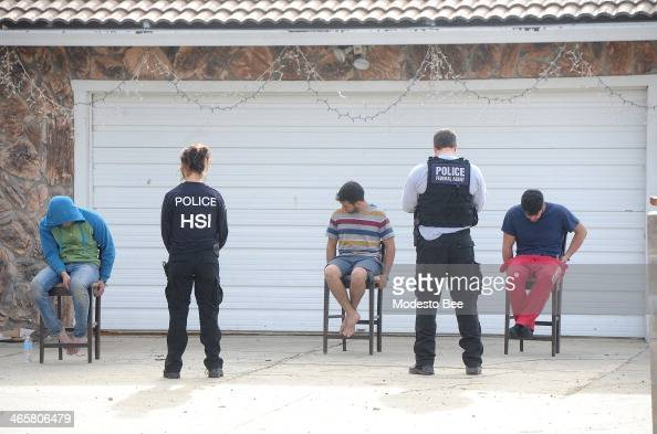 Federal law enforcement agents detain a group of young men at a home on the 1000 block of Almond Avenue in rural Patterson Calif Tuesday morning on...