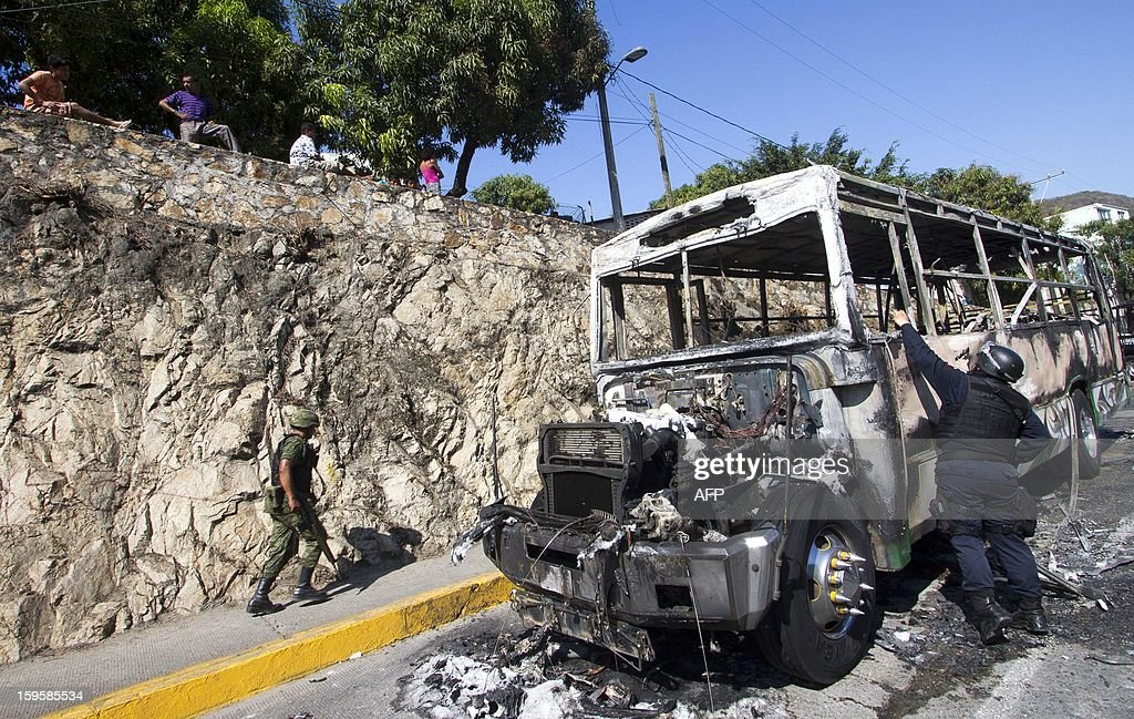 A Federal Police officer takes pictures in the crime scene after a bus was set ablaze in Mozimba neighborhood, Acapulco, Guerrero State, Mexico on January 16, 2013. The bus was attacked by unkown gunmen who evacuated passengers and killed the driver and his 14-year-old assistant before setting fire to the bus. AFP PHOTO/ Pedro Pardo