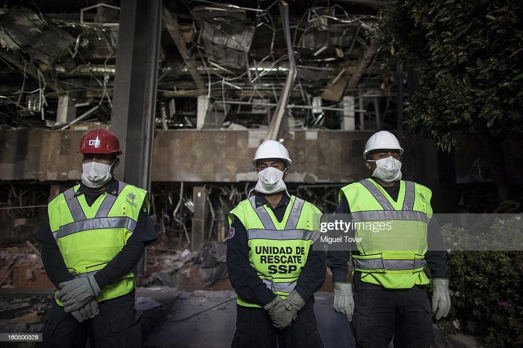 Federal police officers stand guard at the PEMEX administrative building after the explotion on February 01, 2013 in Mexico City, Mexico. Pemex is stepping up security at oil production facilities as authorities investigate a blast that killed at least 33 people at the state-owned company's headquarters in Mexico City.