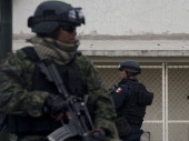 A federal policeman and a soldier stand guard before the presentation of Juan Manuel Rodriguez Garcia aka 'Juan Perros' an alleged leader of the Gulf...