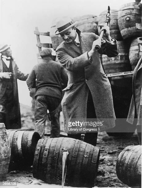Federal policemen destroying a rumrunner's cargo in San Francisco during prohibition Pickaxes are being used to pierce the barrels and let the rum...