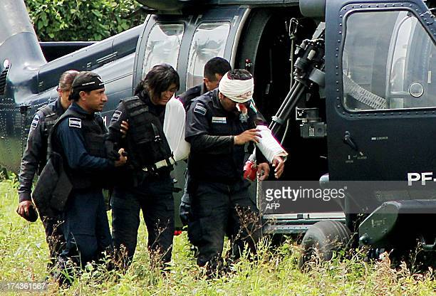 Federal policemen help two wounded mates to descend from a gunship Black Hawk helicopter after their arrival in Aquila Michoacan state on July 24...