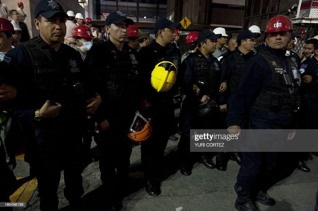 Federal policemen stand guard at the headquarters of state-owned Mexican oil giant Pemex in Mexico City on January 31, 2013, following a blast inside the building. An explosion rocked the skyscraper, leaving up to 25 dead and 101 injured, as a plume of black smoke billowed from the 54-floor tower, according to official sources.