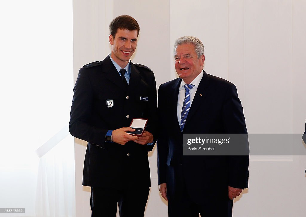 Federal President Joachim Gauck (R) awards Arnd Peiffer, Germany's silver medalist for the the men's 4 x 7.5 km Relay the Silbernes Lorbeerblatt during the Silbernes Lorbeerblatt Award Ceremony at Schloss Bellevue on May 8, 2014 in Berlin, Germany.