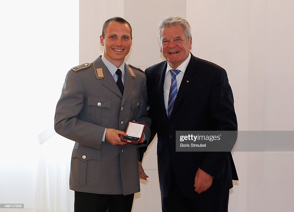 Federal President Joachim Gauck (R) awards Erik Lesser, Germany's silver medalist for the the men's 4 x 7.5 km Relay the Silbernes Lorbeerblatt during the Silbernes Lorbeerblatt Award Ceremony at Schloss Bellevue on May 8, 2014 in Berlin, Germany.