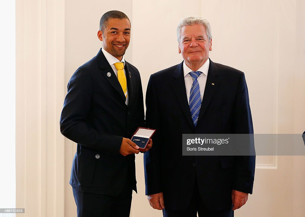 Federal President Joachim Gauck (R) awards Robin Szolkowy, bronze medalist of the Figure Skating Pairs Free Skating the Silbernes Lorbeerblatt during the Silbernes Lorbeerblatt Award Ceremony at Schloss Bellevue on May 8, 2014 in Berlin, Germany.
