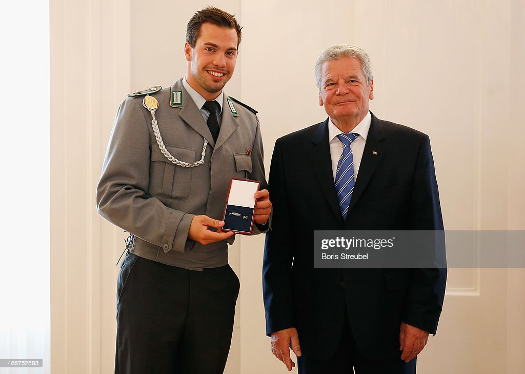 Federal President Joachim Gauck (R) awards Tobias Wendl, gold medalist of the men's Luge Doubles and gold medalist of the Luge Team Relay the Silbernes Lorbeerblatt during the Silbernes Lorbeerblatt Award Ceremony at Schloss Bellevue on May 8, 2014 in Berlin, Germany.