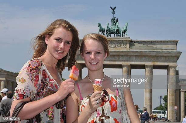 Federal Republic of Germany Berlin Mitte young girls eating ice cream in front of Brandenburg Gate