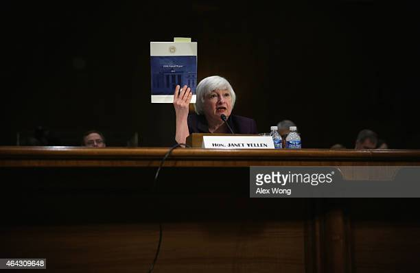 Federal Reserve Board Chair Janet Yellen holds up a copy of the 100th annual report of the Federal Reserve from 2013 as she testifies during a...