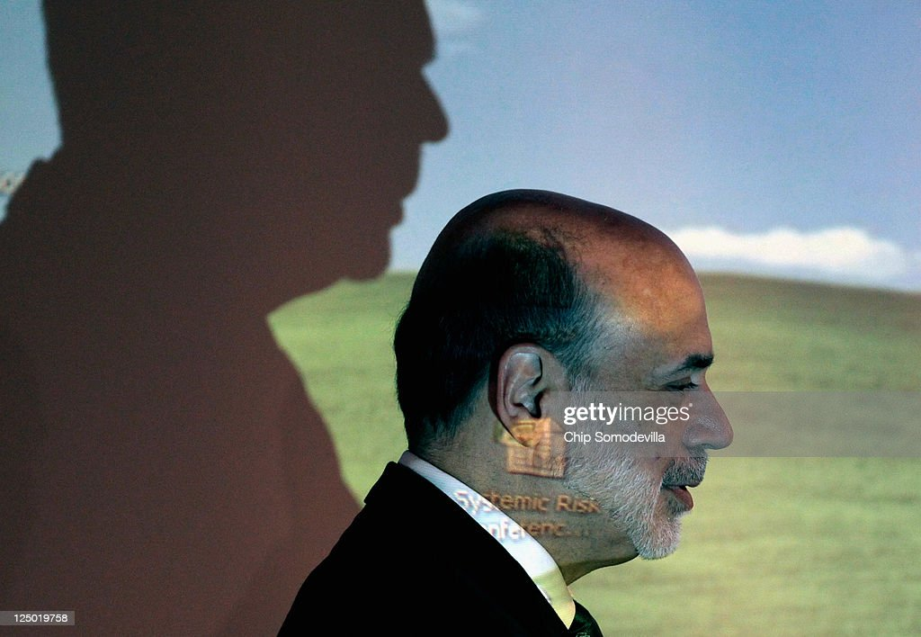Federal Reserve Board Chairman <a gi-track='captionPersonalityLinkClicked' href=/galleries/search?phrase=Ben+Bernanke&family=editorial&specificpeople=568098 ng-click='$event.stopPropagation()'>Ben Bernanke</a> walks through the light of a computer projector before delivering remarks September 15, 2011 in Washington, DC. Bernanke made brief opening remarks for a conference on 'Regulation of Systemic Risk.'