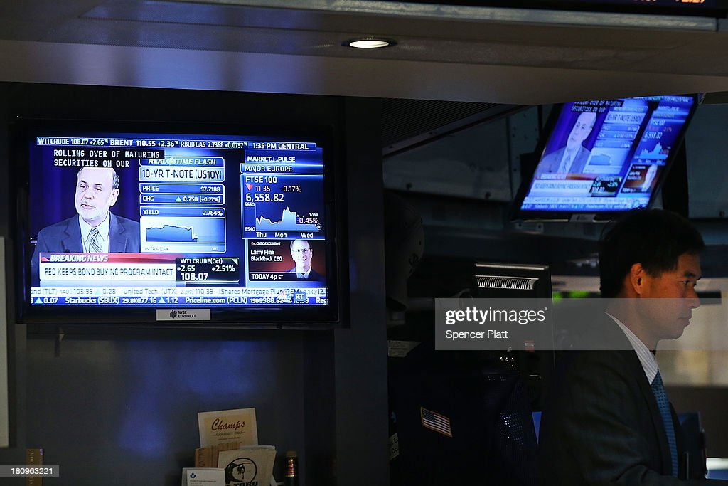 Federal Reserve Chairman Ben Bernanke, speaking at a news conference, is seen on a television screen on the floor of the New York Stock Exchange on September 18, 2013 in New York City. As the economic outlook continues to remain precarious for the central bank, the Federal Reserve announced that it will continue its bond-buying program in full for at least another month. News of the decision sent stocks soaring with the Dow Jones industrial average up over 160 points in afternoon trading.
