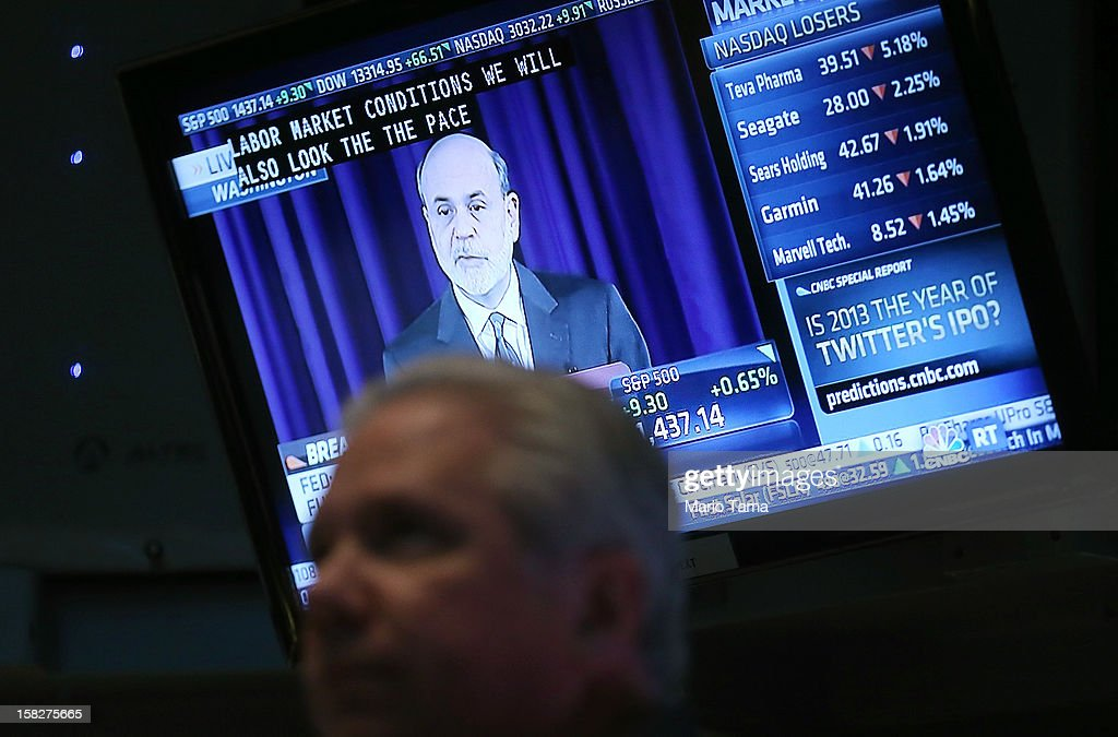 Federal Reserve Chairman Ben Bernanke's press conference is broadcasted as a trader stands on the floor of the New York Stock Exchange on December 12, 2012 in New York City. Bernanke announced the Federal Reserve will tie its bond purchase program to the rate of the nation's unemployment.