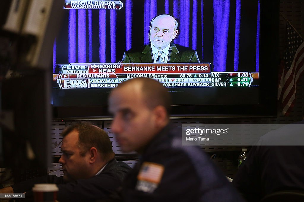 Federal Reserve Chairman Ben Bernanke's press conference is broadcasted as traders work on the floor of the New York Stock Exchange on December 12, 2012 in New York City. Bernanke announced the Federal Reserve will tie its bond purchase program to the rate of the nation's unemployment.