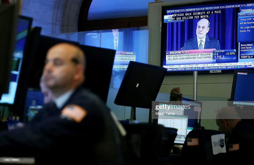 Federal Reserve Chairman Ben Bernanke's press conference is broadcastedas traders work on the floor of the New York Stock Exchange on December 12, 2012 in New York City. Bernanke announced the Federal Reserve will tie its bond purchase program to the rate of the nation's unemployment.
