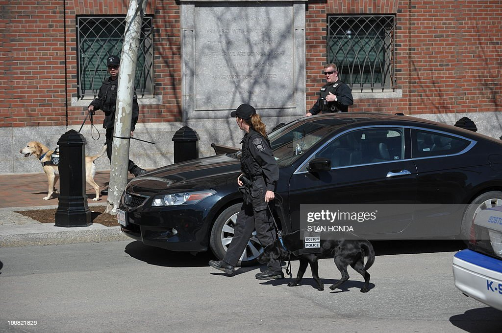US federal security K-9 officers guard the Moakley Federal Courthouse in Boston on April 17, 2013, as it is evacuated. Officials said a bomb threat had been received. AFP PHOTO/Stan Honda