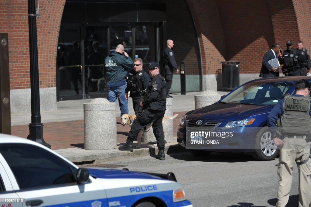 US federal security officers guard the Moakley Federal Courthouse in Boston on April 17, 2013, as it is evacuated. Police on Wednesday evacuated the federal courthouse in Boston which has been under increased scrutiny since the deadly bomb attacks earlier this week at the city's marathon. An AFP reporter at the scene said scores of people were ordered out of the building near the Boston seafront and two fire trucks were present. Police moved onlookers more than 100 feet (30 meters) back from the building, but there was no immediate sign of an emergency. AFP PHOTO/Stan Honda