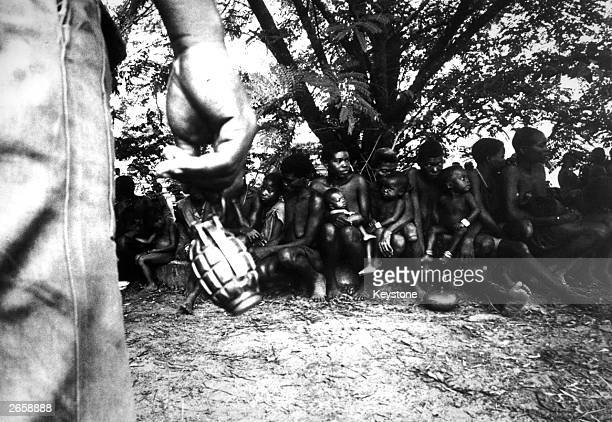 A federal soldier swings a hand grenade by its release pin while guarding Ibo women prisoners and their children in Nigeria during the Biafran War