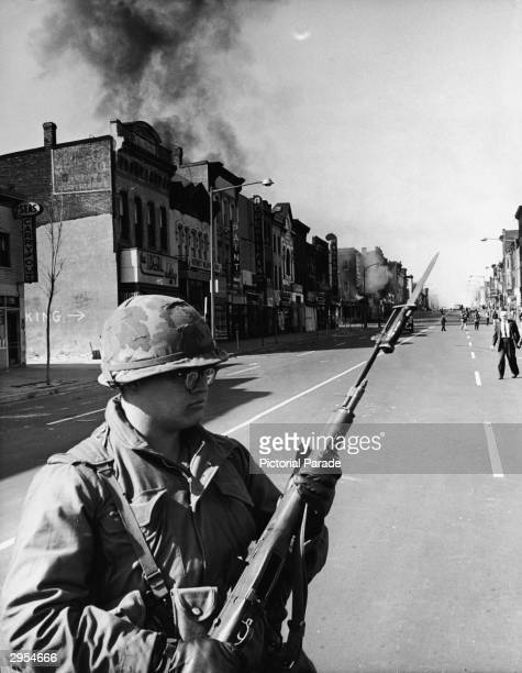 A federal trooper stands on watch and holds a rifle on a street during riots which took place after the assasination of Martin Luther King Jr...
