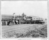 Photograph of federal troops posing holding rifles on top of a Pullman engine or locomotive to restore order during the Pullman railroad workers...