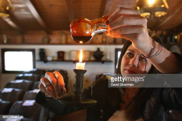 Federica Gibellini uses candlelight to check the colors of aging balsamic vinegar taken from a wooden cask at Acetaia Leonardi on March 27 2017 in...