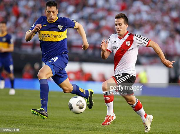 Federico Andrada of River Plate fights for the ball with Claudio Perez of Boca Juniors during a match between River Plate and Boca Juniors as part of...