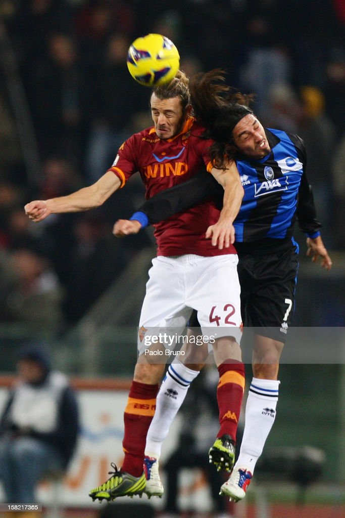 Federico Balzaretti (L) of AS Roma competes for the ball with Ezequiel Schelotto of Atalanta BC during the TIM Cup match between AS Roma and Atalanta BC at Olimpico Stadium on December 11, 2012 in Rome, Italy.
