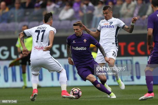 Federico Bernardeschi of ACF Fiorentina battles for the ball with Rade Krunic and Marcel Buchel of Empoli FC during the Serie A match between ACF...