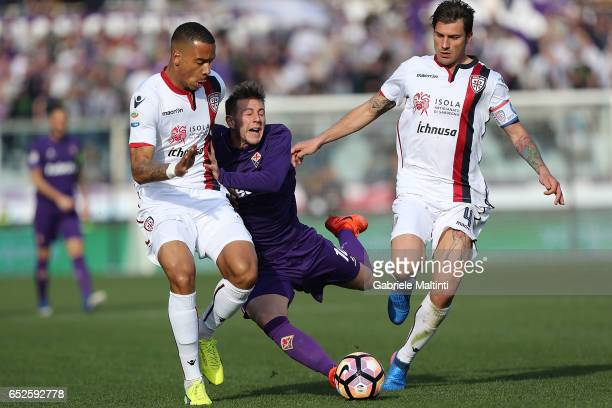 Federico Bernardeschi of ACF Fiorentina in action against Senna Miague and Daniele Dessena of Cagliari Calcio during the Serie A match between ACF...