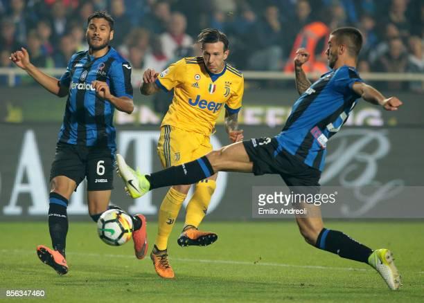 Federico Bernardeschi of Juventus FC is challenged by Leonardo Spinazzola and Jose Palomino of Atalanta BC during the Serie A match between Atalanta...