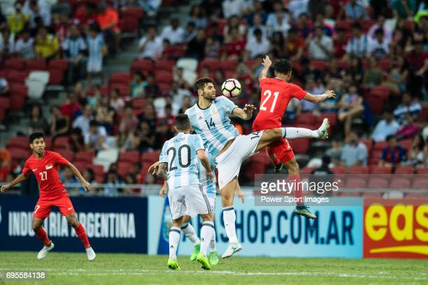 Federico Fazio of Argentina trips up with Safuwan Baharudin of Singapure during the International Test match between Argentina and Singapore at...
