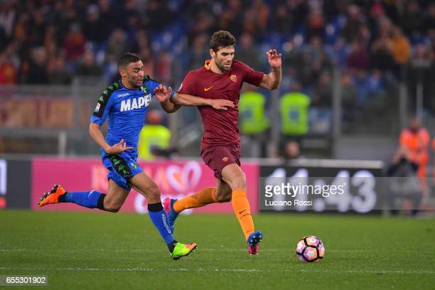 Federico Fazio of AS Roma is challenged by Gregoire Defrel of US Sassuolo during the Serie A match between AS Roma and US Sassuolo at Stadio Olimpico...