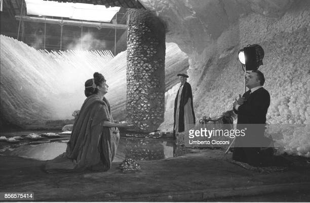 Federico Fellini on set with two actors while directing the movie 'Satyricon' in 1969