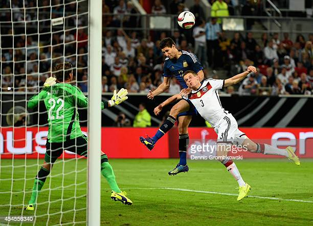 Federico Fernandez of Argentina heads the third goal under the pressure of Matthias Ginter of Germany during the international friendly match between...
