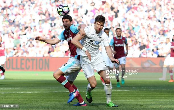 Federico Fernandez of Swansea City is challenged by Jonathan Calleri of West Ham United during the Premier League match between West Ham United and...