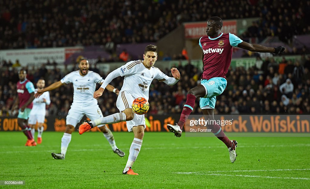Federico Fernandez of Swansea City shoots on goal under pressure from Cheikou Kouyate of West Ham during the Barclays Premier League match between Swansea City and West Ham United at the Liberty Stadium on December 20, 2015 in Swansea, Wales.
