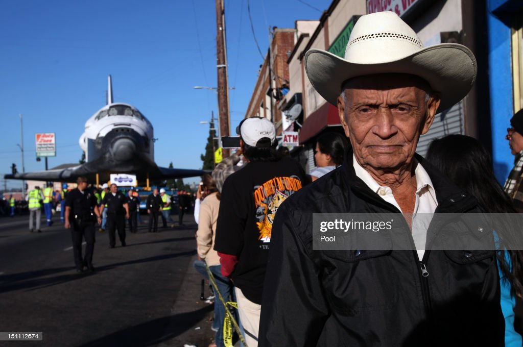 Federico Gonzales is among the many spectators to watch the movement of Space Shuttle Endeavour on Martin Luther King Boulevard to the California Science Center on October 14, 2012 in Los Angeles, California. Endeavour is on its last mission - a 12-mile creep through city streets, past an eclectic mix of strip malls, mom-and-pop shops, tidy lawns and faded apartment buildings. Its final destination is the California Science Center in South Los Angeles where it will be put on display. NASA's Space Shuttle Program ended in 2011 after 30 years and 135 missions.