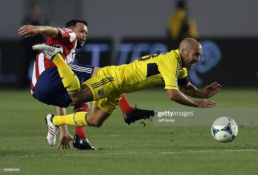 Federico Higuain #33 of Columbus Crew is tripped up by Bobby Burling #2 of Chivas USA in the second half at The Home Depot Center on March 2, 2013 in Carson, California. The Crew defeated Chivas USA