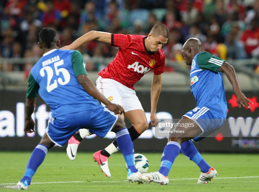 Federico Macheda of Manchester United clashes with Bukasa Kasonga of AmaZulu FC during the pre-season friendly between AmaZulu FC and Manchester United at Moses Mabhida Stadium on July 18, 2012 in Durban, South Africa.