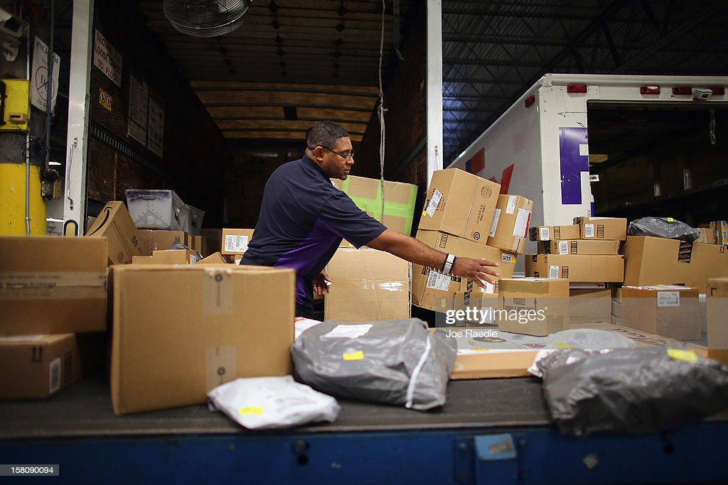 FedEx employee, James Johnson, sorts through items being shipped through the Fedex World Service Center on December 10, 2012 in Doral, Florida. FedEx Corp. expects today to be the busiest shippping day of the year when 19 million packages are expected to move through their system.