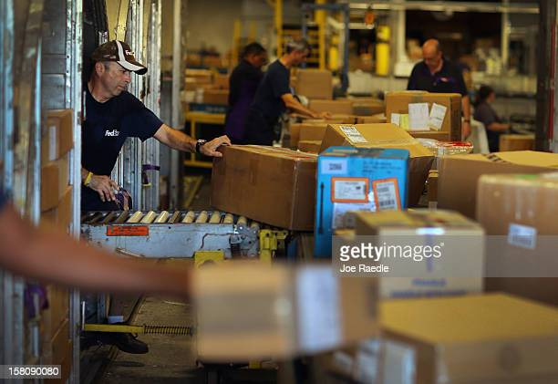 FedEx employee Javier Belisario sorts through items being shipped through the Fedex World Service Center on December 10 2012 in Doral Florida FedEx...