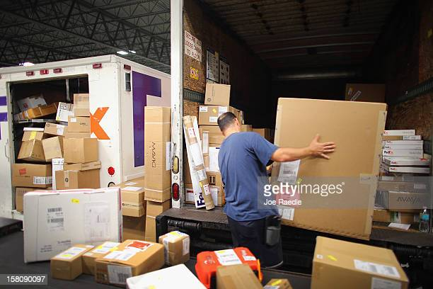 FedEx employee Ron Shaheen loads items being shipped into a truck for delivery at the Fedex World Service Center on December 10 2012 in Doral Florida...