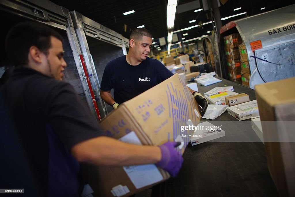 FedEx employees, Denis Sanchez (L) and Nate Arroyo sort through items being shipped through the Fedex World Service Center on December 10, 2012 in Doral, Florida. FedEx Corp. expects today to be the busiest shippping day of the year when 19 million packages are expected to move through their system.