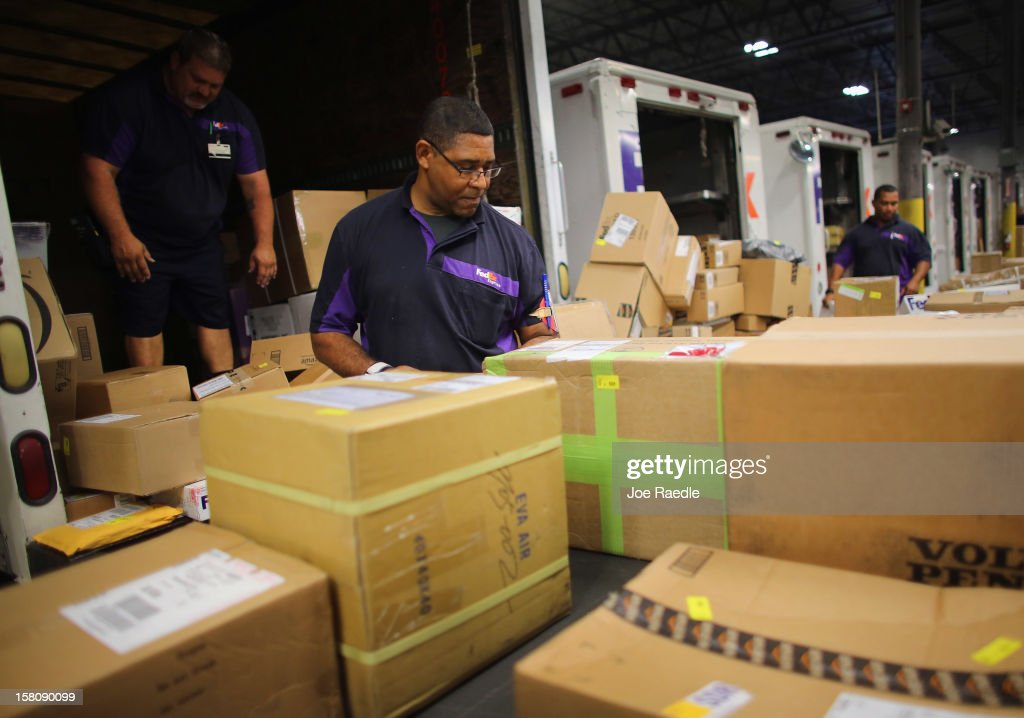 FedEx employees, James Johnson and others, sort through items being shipped through the Fedex World Service Center on December 10, 2012 in Doral, Florida. FedEx Corp. expects today to be the busiest shippping day of the year when 19 million packages are expected to move through their system.